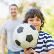 Stock Photo: Father and son playing football in park