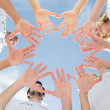 Stock Photo: Volunteers with hands together against blue sky