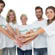 Group portrait of happy volunteers with hands together — Stock Photo