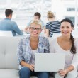Women using laptop with colleagues in background at creative off — Stock Photo