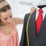 Female fashion designer measuring suit on dummy — Stock Photo #39192905