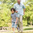 Grandfather and son running on grass in park — Stock Photo