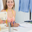 Smiling female fashion designer working on her designs — Stock Photo #39192961