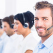 Business colleagues with headsets in a row — Stock Photo #39193233