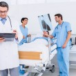 Stock Photo: Doctors holding reports by patient at hospital