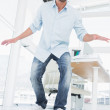 Full length of a happy young man skateboarding in office — Stock Photo