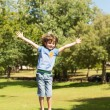 Stock Photo: Happy boy jumping high on trampoline in the park