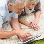 Smiling senior couple using digital tablet at park — Stock Photo