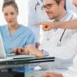 Group of concentrated doctors using laptop together — Stock Photo #39194795