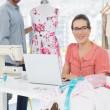 Woman using laptop with fashion designer working at studio — Stock Photo