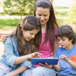 Woman with kids using digital tablet in park — Stock Photo