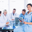 Female surgeon holding reports with colleagues in meeting — Stock Photo #39195043
