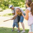 Family playing baseball in park — Stock Photo