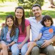 Couple with young kids sitting on park bench — Stock Photo
