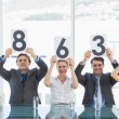 Group of panel judges holding score signs — Stock Photo