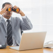 Businessman with binoculars in front of laptop at office — Stock Photo