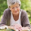 Senior woman reading a book at park — Stock Photo #39196355