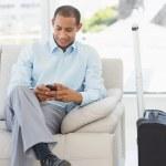 человек, сидя на диване, отправка текста, ждут, чтобы отправиться на бизнес — Стоковое фото #39196605