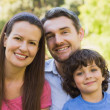 Close-up of a smiling couple with son in park — Stock Photo