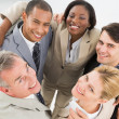 Close business team embracing in a circle smiling up at camera — Stock Photo