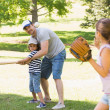 Family playing baseball in the park — Stock Photo