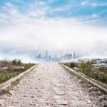 Stony path leading to misty cityscape — Stock Photo #39197947