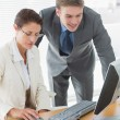 Cusiness couple using computer at office desk — Stock Photo