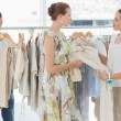 Stock Photo: Seller helping shopper choose clothes in store