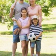 Family of four holding baseball bat and ball in park — Stock Photo
