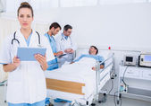 Doctor using digital tablet with colleagues and patient — Stock Photo