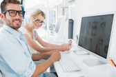 Smiling casual young couple working on computer — Stock Photo
