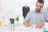 Fashion designer working on his designs in studio — Stock Photo