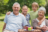 Senior couple and granddaughter with picnic basket at park — Stock Photo