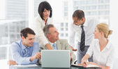 Happy business team gathered around laptop talking — Stock Photo