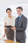 Confident business colleagues with clipboard at office — Stockfoto