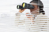Businesswoman peeking with binoculars through blinds — Stock Photo