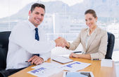 Smartly dressed colleagues shaking hands in a business meeting — Stock Photo