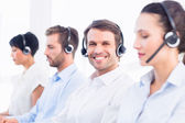 Business colleagues with headsets in a row — Foto Stock