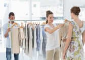 Seller helping shopper choose clothes in store — Stock Photo