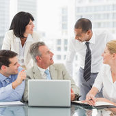 Happy business team gathered around laptop chatting — Stock Photo