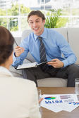 Happy businessman scheduling with colleague sitting on sofa — Stock Photo