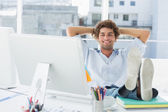 Relaxed casual man with legs on desk in bright office — Stock Photo