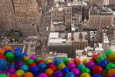 Many colourful balloons above city — Stock Photo