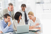 Happy business people gathered around laptop talking — Stock Photo