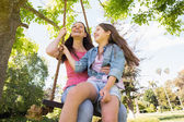 Happy mother and daughter on swing — Stock Photo