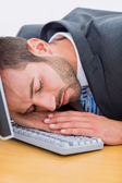 Businessman resting with head over keyboard at desk — Stock Photo