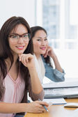 Portrait of two casual female artists working at desk — Stock Photo