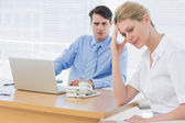 Upset businesswoman with man working on laptop — Stock Photo