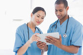 Surgeons looking at digital tablet in hospital — Stock Photo
