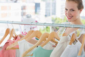 Happy female customer selecting clothes in store — Stock Photo